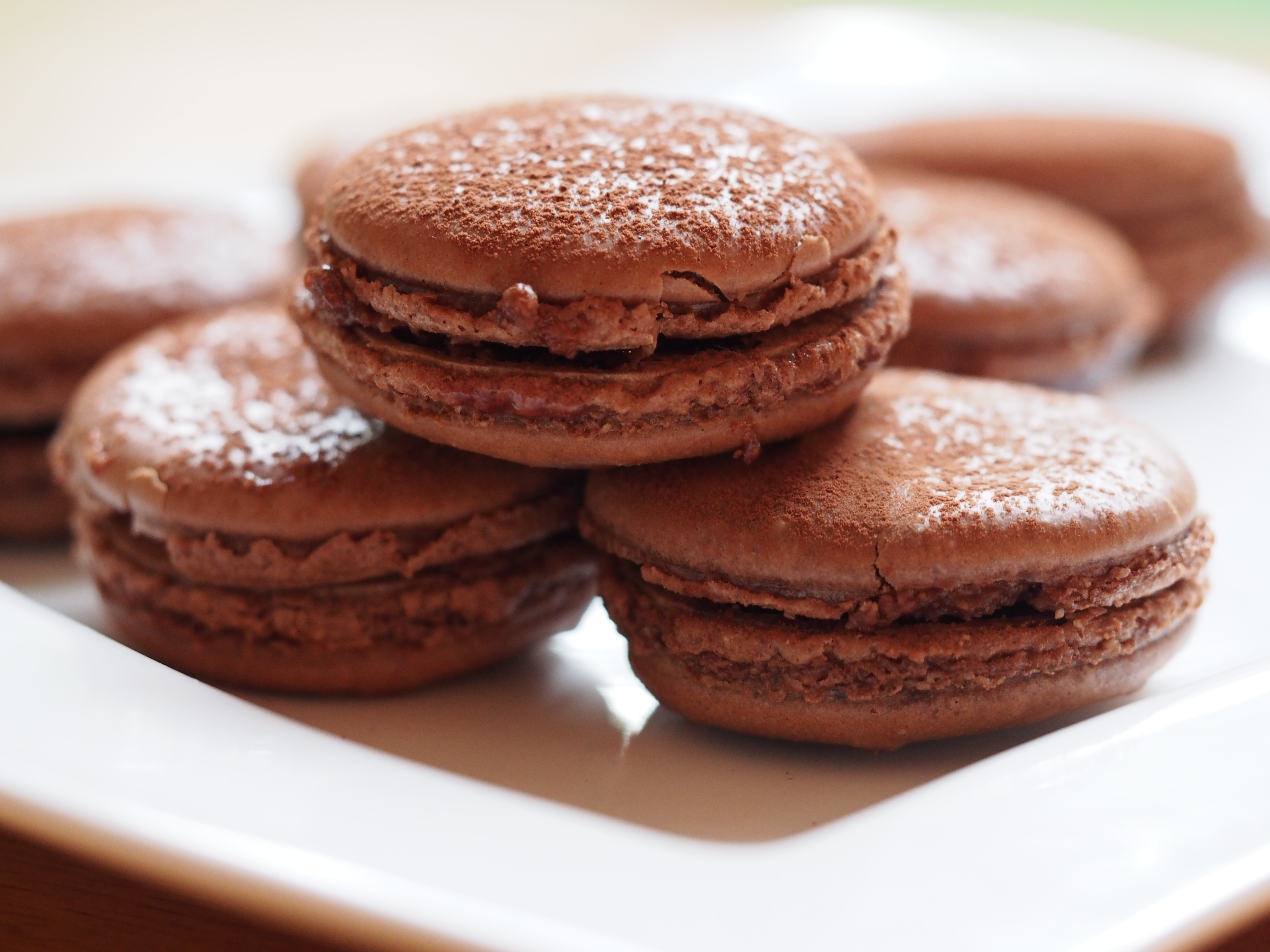 voila beautiful chocolate macarons with raspberry jam filling dusted ...